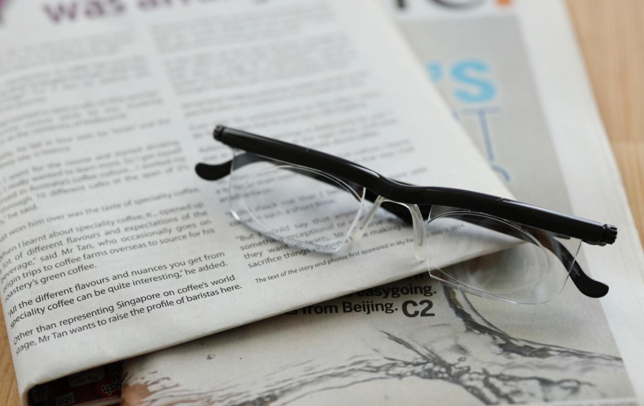 新聞の上に眼鏡が置かれた画像